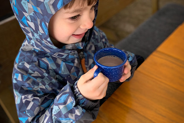 A Small Child Holds A Steaming Hot Cocoa On A Winter Sleigh Ride
