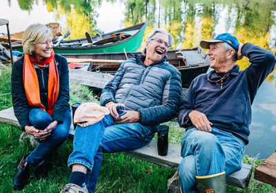 A Group of Adults Laughs Together At A Riverside Camp On The Snake River In Jackson Hole