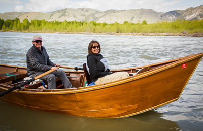 A Couple Drifts Along The Snake River In A Vintage Wooden Dory In Jackson Hole