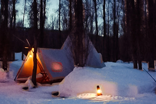 The Warm Glow Of A Lantern Lights The Entrance To A Winter Tipi Camp
