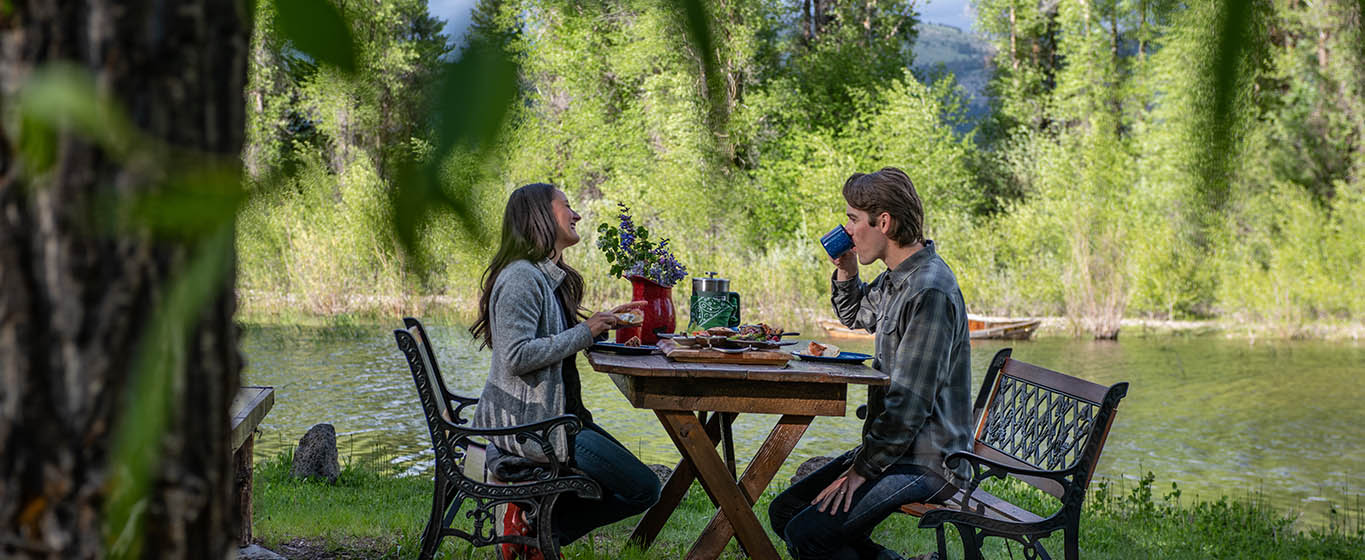 A Couple Enjoys A Gourmet Breakfast Outdoors Next To The Snake River In Jackson Hole Wyoming